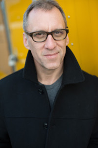 Author Drew Chapman wearing a black overcoat with the collar turned up and standing in front of a mustard yellow bankground