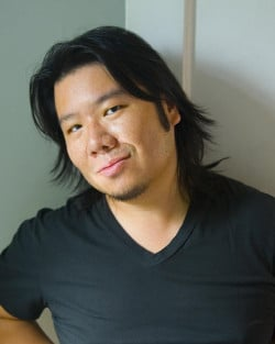 Kevin Kwan wearing a black v-neck t-shirt and with his long black hair loose and flowing around his shoulders