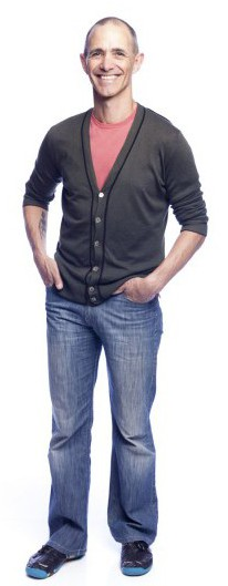 Full body shot of Andy Griffiths wearing jeans and a grey cardigan buttoned up at the front